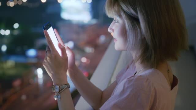 szene einer lächelnden asiatischen frau mit smartphone auf balkon mit nachtblick - person gemischter abstammung stock-videos und b-roll-filmmaterial
