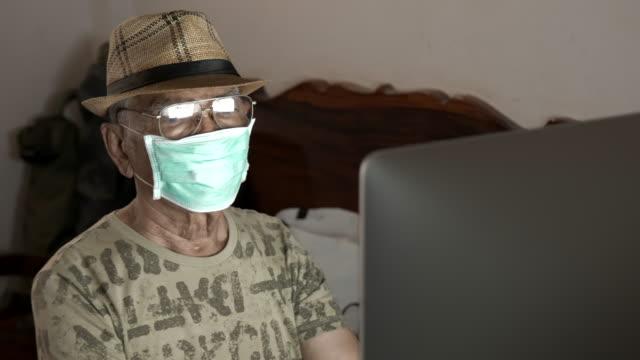 vidéos et rushes de scène de mâle aîné asiatique portant le masque pour protéger le coronavirus ou le covid-19 utilise le pc d'ordinateur à la maison pendant le verrouillage pandémique de coronavirus, concept de travail à la maison - seniornaute