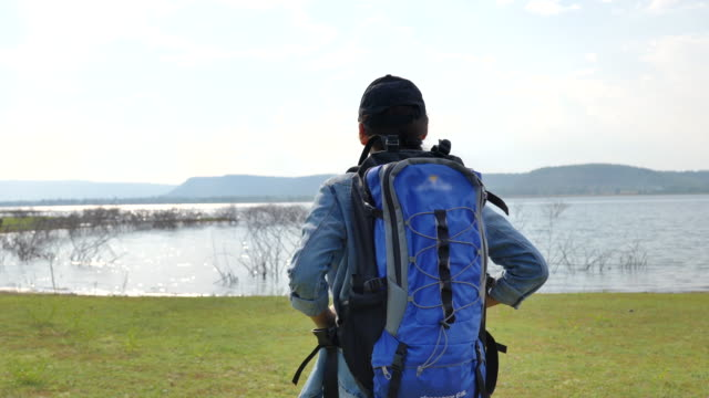 Scene of asian woman backpacker is walking and enjoying view nature near the lake in the summer holidays. She is happy and have fun on holidays, Relaxation moment. Concept of teen natural everyday life outdoors