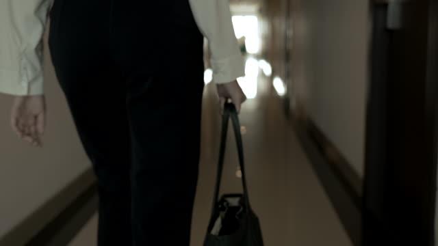 vidéos et rushes de scène de femme asiatique retenant son sac quand elle marchant hors de la maison au travail - porte documents