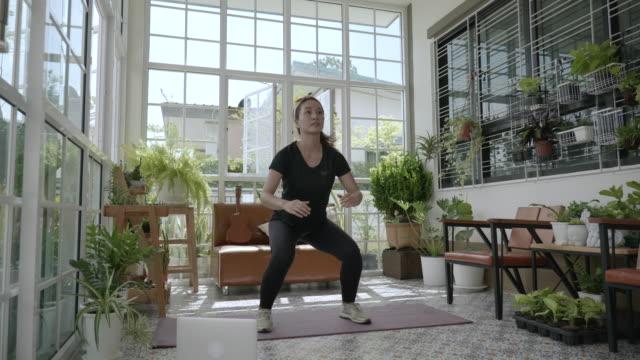 vidéos et rushes de scène de femme asiatique qu'elle exerce à la maison, le mode de vie des gens tandis que l'épidémie du coronavirus ou covid-19, le verrouillage des personnes, la distanciation sociale des gens, rester à la maison des gens - quête de beauté