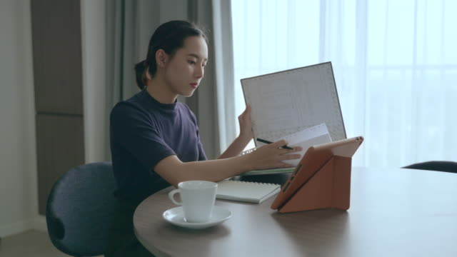 scene of asian woman using her tablet to work at home - document stock videos & royalty-free footage