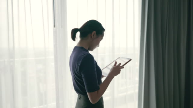 scene of asian woman using her tablet while she walking near the window - bathrobe stock videos & royalty-free footage