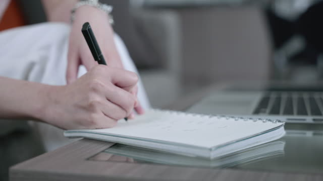 scene of asian woman's hand writing on a notebook while learning at home - list stock videos & royalty-free footage