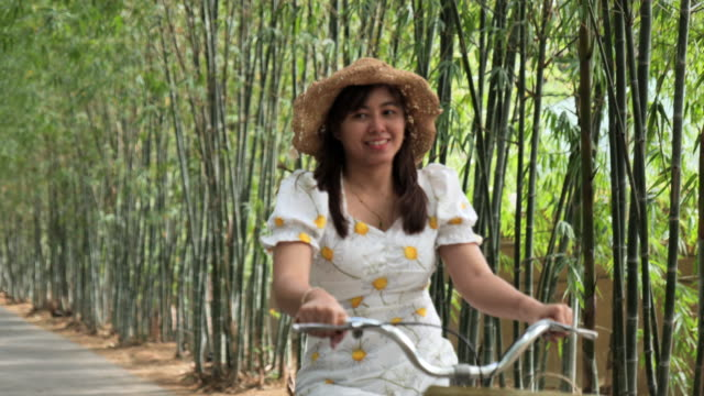 scene of cute asian woman ride bicycle on the road at garden bamboo - bamboo plant stock videos & royalty-free footage