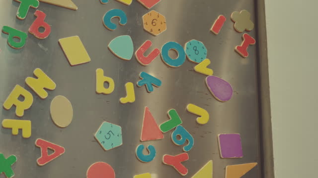 scene of detail of colorful magnets on a fridge door. make by father's and mother's with son playing at home, concept of family objects - magnet stock videos & royalty-free footage