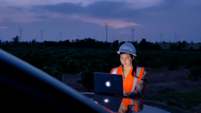 Scene of engineer asian woman using the laptop at evening t to evaluate a wind turbine, Concept of Renewable energy plants