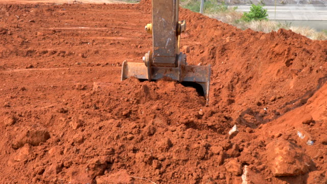 scene of excavator bucket digging into the soil at the sunny construction sit - pushing stock videos & royalty-free footage