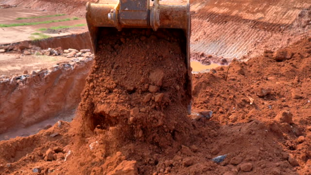 scene of excavator bucket digging into the soil at the sunny construction site, slow motion - surface mine stock videos and b-roll footage