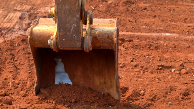 scene of excavator bucket digging into the soil at the sunny construction site - surface mine stock videos and b-roll footage