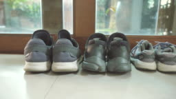 Scene of father's shoes and mother's shoes next to son shoes near front the door at home, Concept of family objects