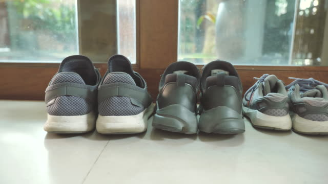 scene of father's shoes and mother's shoes next to son shoes near front the door at home, concept of family objects - shoe stock videos & royalty-free footage