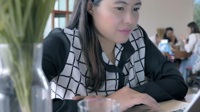 vidéos et rushes de scène de femme asiatique freelance travaillant au café, femme asiatique d'affaires travaillant sur l'ordinateur portatif au café, concept de femme asiatique freelance de mode de vie travaille au café - répondre
