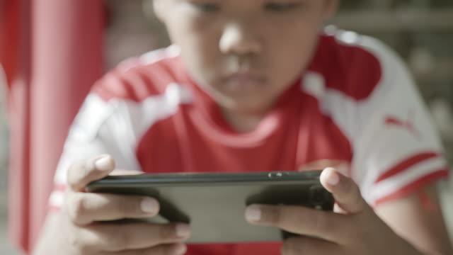 vidéos et rushes de scène de petit garçon heureux jouant sur des jeux mobiles en ligne, rester à la maison, distanciation sociale, protection de covide-19 ou coronavirus - commodité