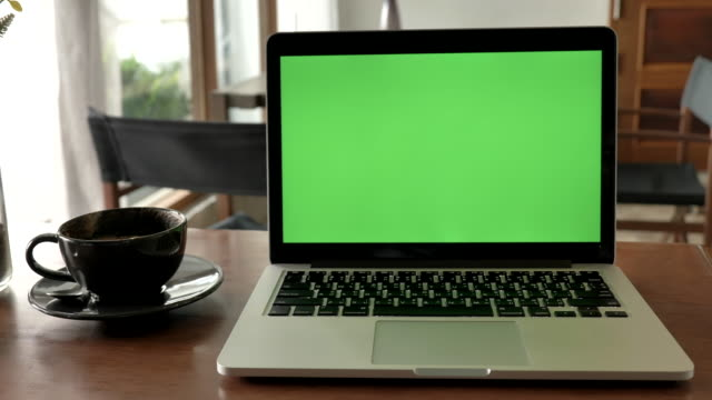 scene of  laptop computer showing green chroma key screen stands on a desk in the coffee shop. technology in the background , concept of technology background - coffee shop background stock videos & royalty-free footage