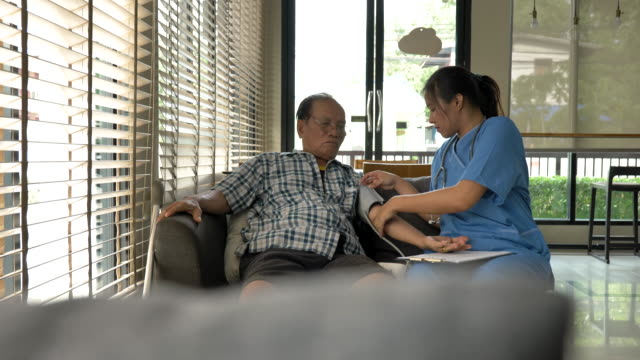Scene of nurse is taking care helps senior asian man patient check pulse with blood pressure gauger at home, Concept senior of home healthcare, Nurse is taking care senior patients at home