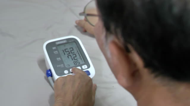scene of senior asian male measures his pressure at home - blood pressure gauge stock videos & royalty-free footage