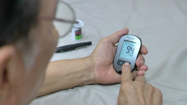 scene of senior asian male patient with diabetes using blood glucose meter at home, viewing blood glucose results - glucose stock videos & royalty-free footage