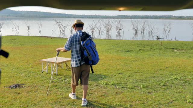 scene of senior asian male walking and backpack with stick is relaxing and enjoying view near the lake in the summer holidays. he is happy and have fun on holidays, relaxation moment - outdoor chair stock videos & royalty-free footage