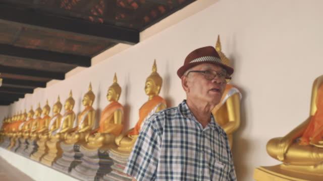 アジアの先輩男性がアユタヤの寺院で旧市街を楽しむシーン、シニアソロ旅行のコンセプト - ワットチャイワタナラム点の映像素材/bロール