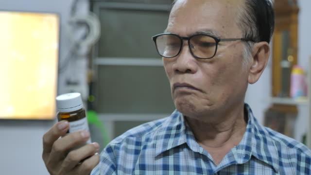 vídeos y material grabado en eventos de stock de escena del hombre asiático senior poniéndose gafas para leer su frasco de prescripción - receta instrucciones