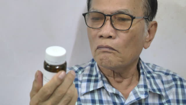 scene of senior asian man putting on glasses to read her prescription bottle at home - pill bottle stock videos & royalty-free footage