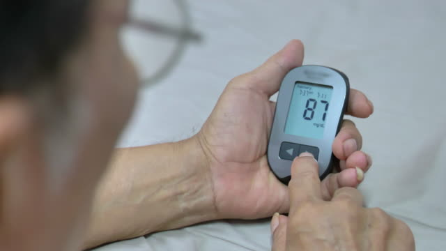 scene of senior man patient with diabetes using blood glucose meter. viewing blood glucose results - glucose stock videos & royalty-free footage
