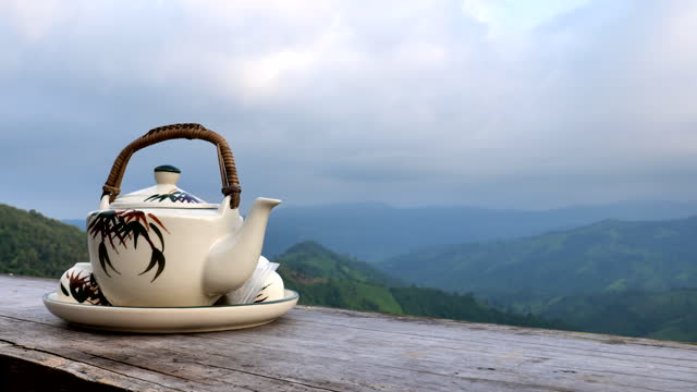 scene of teapot in the morning with fog and mountain background - teapot stock videos & royalty-free footage