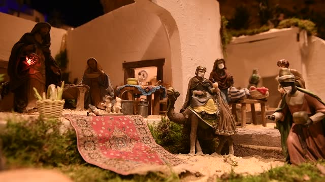 scene of the birth of jesus christ with the offering of the wise man melchior, who has been given a face mask in the monumental nativity scene of... - キリスト降誕点の映像素材/bロール