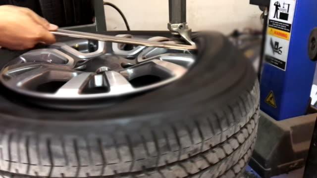 stockvideo's en b-roll-footage met scène van band wisseling bij auto service - piercen