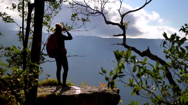 vídeos y material grabado en eventos de stock de escena de mujer usando prismáticos en el bosque, mujer viajar y usar binoculares buscando pájaro en el bosque, cámara lenta - mochila bolsa