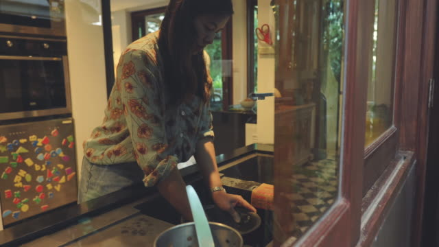 scene of young asian is washing rice cooker in the kitchen at home. - washing up stock videos & royalty-free footage