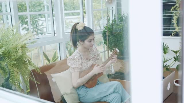 vídeos de stock, filmes e b-roll de cena de jovem asiática tocando música de guitarra ukulele e usando tutorial online de vídeo de computador portátil em casa, ficando em casa e longe de outros, lockdown, covid-19 ou coronavirus, conceito de teleconferência com música - ukulele