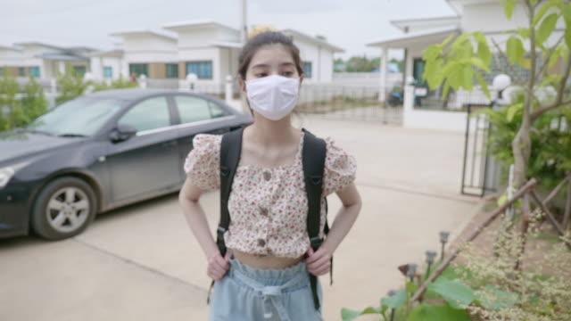 コロナウイルスが家の中に入るのを防ぐためにマスクを着用した若いアジアの女性のシーン - スポーツ用語点の映像素材/bロール
