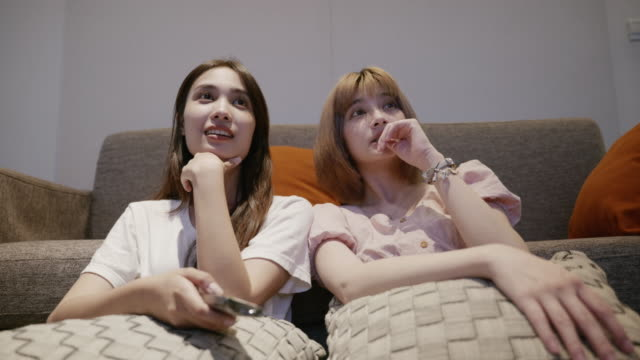 scene of young asian women sitting on couch while they are watching tv together - smooth stock videos & royalty-free footage