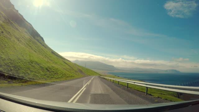 vídeos de stock, filmes e b-roll de cena pov da rota vá ao litoral na terra ocidental em islândia, vista de dirigir o carro na estrada em islândia, vista da janela dianteira do carro, conceito de viagens de estrada do feriado - ponto de vista de carro