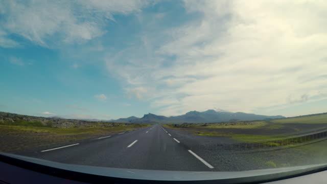 stockvideo's en b-roll-footage met scene pov van de route naar westland met kijkt uitzicht snaefellsjokull gletsjer-begrensd, uitzicht op rijdende auto op de weg in ijsland, uitzicht vanaf auto voorruit, concept van vakantie road trips - car point of view