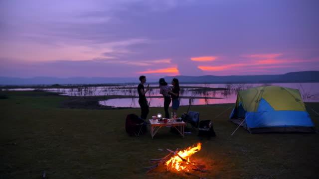 十代の若者たちのシーンスローモーショングループはキャンプファイヤーと夏の休暇で湖の近くに夕日を見てテントの前で一緒に楽しんでいます。彼らは幸せであり、休日、リラクゼーショ� - テント点の映像素材/bロール