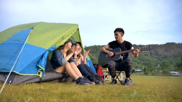 在暑假裡, 一群朋友的慢動作正在湖邊的帳篷前唱歌和欣賞。他們是快樂的, 在假期裡玩得很開心, 放鬆的時刻。青少年自然的戶外生活理念 - 東亞人 個影片檔及 b 捲影像