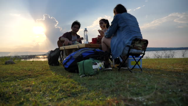 scene slow motion of a group of friends is enjoying picnic and viewing nature near the lake in the summer holidays.they are happy and have fun on holidays, relaxation moment. concept of teen natural everyday life outdoors - repubblica dello zimbabwe video stock e b–roll