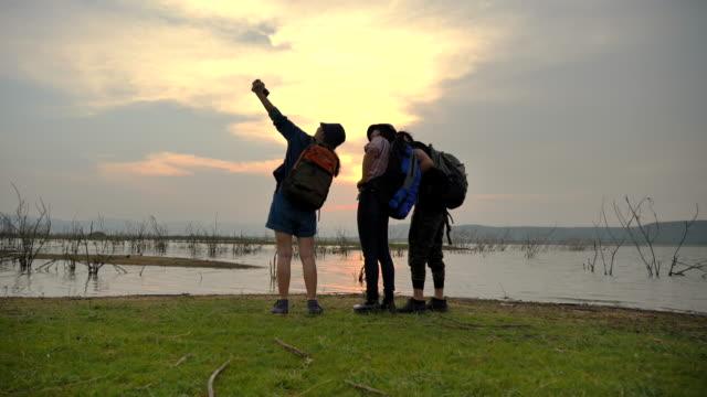 vidéos et rushes de scène slow motion d'un groupe d'adolescents asiatiques prenant selfie près du lac dans les vacances d'été. ils sont heureux et amusez-vous en vacances, moment de détente. concept de la vie quotidienne normale de l'adolescence à l'extérieur - trois personnes