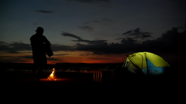 Scene slow motion of asian man backpacker a playing guitar near campfire and enjoying view near the lake in the summer holidays.He is happy and have fun on holidays, Relaxation moment. Concept of teen natural everyday life outdoors