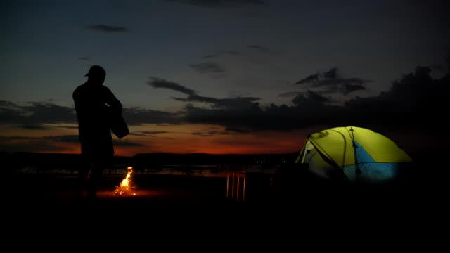 アジア人男性バックパッカーのシーンスローモーションは、キャンプファイヤーの近くにギターを演奏し、夏の休日に湖の近くに景色を楽しみます。彼は幸せで、休日、リラクゼーションの� - テント点の映像素材/bロール