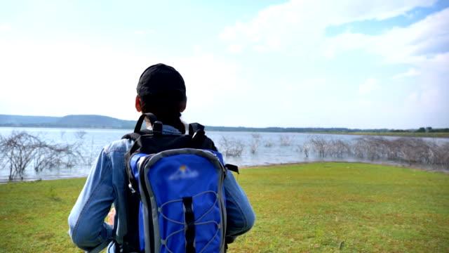 アジア人女性バックパッカーの情景スローモーションは、夏休みに湖の近くで自然を眺めて歩いて楽しむことです。彼女は幸せであり、休日、リラクゼーションの瞬間に楽しみを持っていま� - バックパッカー点の映像素材/bロール