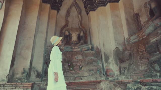 アジアの女性のシーンスローモーションは、アユタヤのチャイワトナララム寺院で旅行旧市街を楽しむ、チャイワトナラム寺院はアユタヤで有名な場所旧市街です - ワットチャイワタナラム点の映像素材/bロール