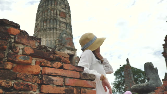 アジアの女性のシーンスローモーションは、アユタヤの寺院で旅行旧市街を楽しむ、寺院でアジアの女性の単独旅行はアユタヤで有名な場所旧市街です - ワットチャイワタナラム点の映像素材/bロール