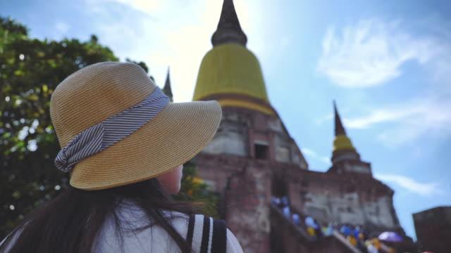 アジアの女性のシーンスローモーションは、アユタヤで寺院で旅行古い都市を楽しんで、アジアの女性は、寺院での一人旅は、アユタヤで有名な場所の旧市街です - ワットチャイワタナラム点の映像素材/bロール