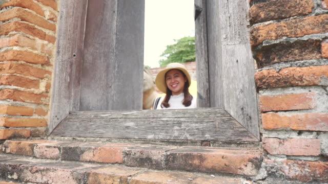 アジアの女性のシーンスローモーションは、アユタヤの寺院で古い街を旅を楽しむ、テンプルでのアジアの女性の一人旅はアユタヤの有名な場所旧市街です - ワットチャイワタナラム点の映像素材/bロール