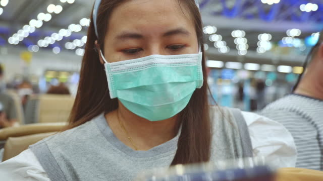 scene slow motion of asian woman wearing mask waiting at airport, use smartphone, asian woman check news and important notifications. fear and panic of coronavirus - notifications stock videos & royalty-free footage