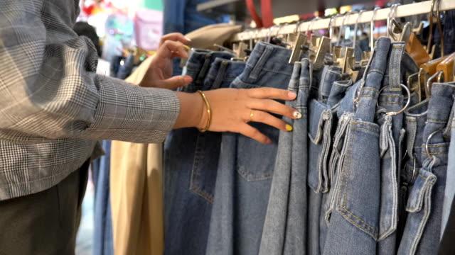 vídeos y material grabado en eventos de stock de escena cámara lenta de la joven asiática comprando jeans en la tienda de ropa, concepto de vacaciones fin de semana, estilo de vida de mujer asiática - vaqueros pantalón